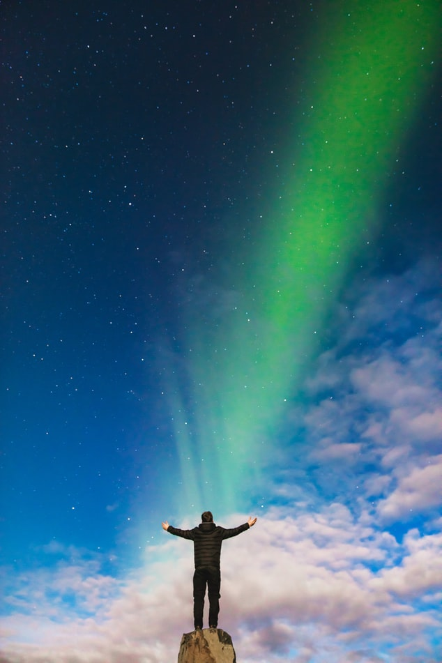 man standing in front of northern lights in Iceland